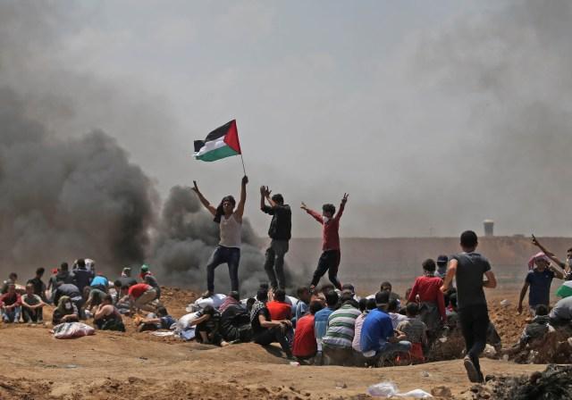 Los palestinos agitan su bandera nacional mientras se manifiestan cerca de la frontera entre Israel y la Franja de Gaza, al este de Jabalia, en contra de la inauguración de la embajada de los Estados Unidos tras su controvertido traslado a Jerusalén el 14 de mayo de 2018. / AFP PHOTO / MOHAMMED ABED