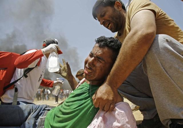 Un palestino asiste a un manifestante herido durante enfrentamientos con las fuerzas de seguridad israelíes cerca de la frontera entre Israel y la Franja de Gaza, al este de Jabalia el 14 de mayo de 2018, mientras los palestinos protestan por la inauguración de la embajada de Estados Unidos tras su controvertido traslado a Jerusalén. / AFP PHOTO / MOHAMMED ABED