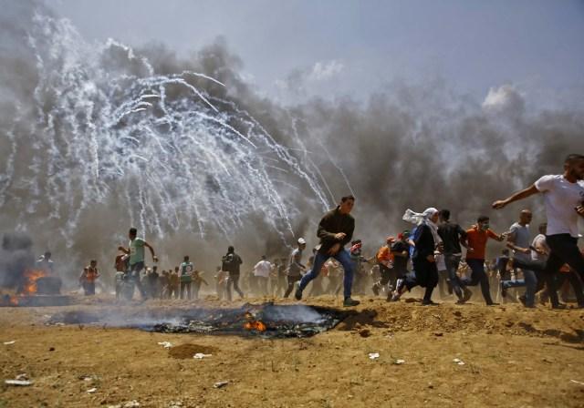 Los palestinos huyen del gas lacrimógeno durante los enfrentamientos con las fuerzas de seguridad israelíes cerca de la frontera entre Israel y la Franja de Gaza, al este de Jabalia el 14 de mayo de 2018, mientras los palestinos protestan por la inauguración de la embajada de Estados Unidos tras su controvertido traslado a Jerusalén. / AFP PHOTO / MOHAMMED ABED