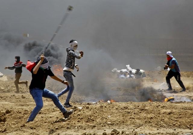 Los manifestantes palestinos utilizan hondas para arrojar piedras contra las fuerzas de seguridad israelíes durante los enfrentamientos cerca de la frontera entre Israel y la Franja de Gaza, al este de Jabalia, el 14 de mayo de 2018, mientras protestan por la inauguración de la embajada de Estados Unidos tras su controvertido traslado a Jerusalén. / AFP PHOTO / MOHAMMED ABED