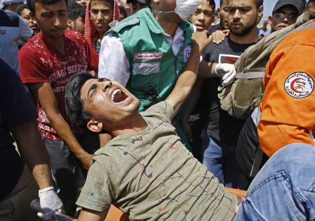 Los servicios de emergencia y los palestinos llevan a un manifestante herido durante los enfrentamientos con las fuerzas de seguridad israelíes cerca de la frontera entre Israel y la Franja de Gaza, al este de Jabalia, el 14 de mayo de 2018, mientras los palestinos protestan por la inauguración de la embajada de Estados Unidos tras su controvertido traslado a Jerusalén. / AFP PHOTO / MOHAMMED ABED