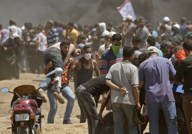 Los palestinos llevan a un manifestante herido durante los enfrentamientos con las fuerzas israelíes cerca de la frontera entre Gaza e Israel al este de la ciudad de Gaza el 14 de mayo de 2018, durante una manifestación el día en que la embajada de EE. UU. Se trasladara a Jerusalén. Estados Unidos traslada su embajada en Israel a Jerusalén el lunes luego de meses de protesta mundial, ira palestina y elogios exuberantes de los israelíes por la decisión del presidente Donald Trump de dejar de lado décadas de precedentes. Existe la preocupación de que las protestas de Gaza a menos de 100 kilómetros (60 millas) de distancia se vuelvan letales si los palestinos intentan dañar o cruzar la valla con francotiradores israelíes posicionados en el otro lado. / AFP PHOTO / MAHMUD HAMS
