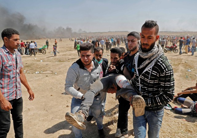 Los palestinos llevan a un manifestante herido durante enfrentamientos con fuerzas israelíes cerca de la frontera entre Gaza e Israel al este de la ciudad de Gaza el 14 de mayo de 2018, mientras los palestinos protestan por la inauguración de la embajada de Estados Unidos tras su controvertido traslado a Jerusalén. Al menos veintiocho palestinos fueron asesinados por disparos israelíes el 14 de mayo cuando decenas de miles protestaron y estallaron enfrentamientos a lo largo de la frontera de Gaza contra el traslado de su embajada a Jerusalén, dijo el Ministerio de Salud de Gaza. Fue el día más mortífero en el conflicto palestino-israelí desde la guerra de 2014 entre el Estado judío y los gobernantes islamistas de Gaza, Hamas. / AFP PHOTO / Thomas COEX