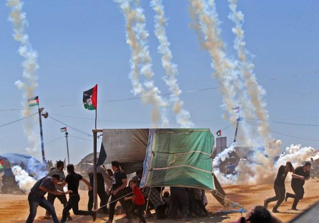 Los palestinos huyen del gas lacrimógeno cerca de la frontera entre Israel y la Franja de Gaza, al este de Jabalia el 14 de mayo de 2018, mientras los palestinos protestan por la inauguración de la embajada de Estados Unidos tras su controvertido traslado a Jerusalén. Decenas de miles de palestinos fueron muertos por disparos israelíes el lunes cuando decenas de miles protestaron y estallaron enfrentamientos a lo largo de la frontera de Gaza contra la transferencia de su embajada a Jerusalén, después de meses de protestas mundiales, ira palestina y elogios exuberantes de los israelíes por la decisión del presidente Donald Trump a un lado décadas de precedente. / AFP PHOTO / Mohammed ABED