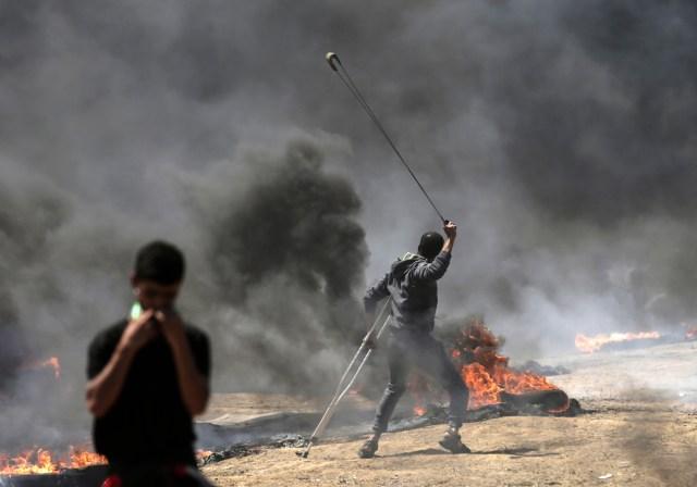 Un palestino usa un tirachinas durante los enfrentamientos con las fuerzas israelíes cerca de la frontera entre Gaza e Israel al este de la ciudad de Gaza el 14 de mayo de 2018, mientras los palestinos protestan por la inauguración de la embajada de Estados Unidos tras su controvertido traslado a Jerusalén. Docenas de palestinos fueron asesinados por disparos israelíes el 14 de mayo cuando decenas de miles protestaron y estallaron enfrentamientos a lo largo de la frontera de Gaza contra la transferencia de su embajada a Jerusalén, luego de meses de protestas globales, ira palestina y elogios exuberantes de los israelíes por el presidente Donald Trump decisión dejando de lado décadas de precedentes. / AFP PHOTO / MAHMUD HAMS