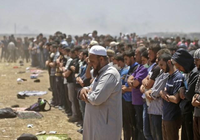 Los palestinos rezan durante los enfrentamientos con las fuerzas israelíes cerca de la frontera entre la franja de Gaza e Israel al este de la ciudad de Gaza el 14 de mayo de 2018, durante una manifestación el día de la mudanza de la embajada de EE. UU. A Jerusalén. Docenas de palestinos fueron asesinados por disparos israelíes el 14 de mayo cuando decenas de miles protestaron y estallaron enfrentamientos a lo largo de la frontera de Gaza contra la transferencia de su embajada a Jerusalén, luego de meses de protestas globales, ira palestina y elogios exuberantes de los israelíes por el presidente Donald Trump decisión dejando de lado décadas de precedentes. / AFP PHOTO / MAHMUD HAMS