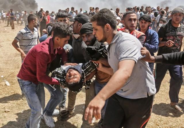 Los palestinos llevan a un hombre herido durante los enfrentamientos con las fuerzas israelíes cerca de la frontera entre Gaza e Israel al este de la ciudad de Gaza el 14 de mayo de 2018, mientras los palestinos protestan por la inauguración de la embajada de Estados Unidos tras su controvertido traslado a Jerusalén. Docenas de palestinos fueron asesinados por disparos israelíes el 14 de mayo cuando decenas de miles protestaron y estallaron enfrentamientos a lo largo de la frontera de Gaza contra la transferencia de su embajada a Jerusalén, luego de meses de protestas globales, ira palestina y elogios exuberantes de los israelíes por el presidente Donald Trump decisión dejando de lado décadas de precedentes. / AFP PHOTO / MAHMUD HAMS