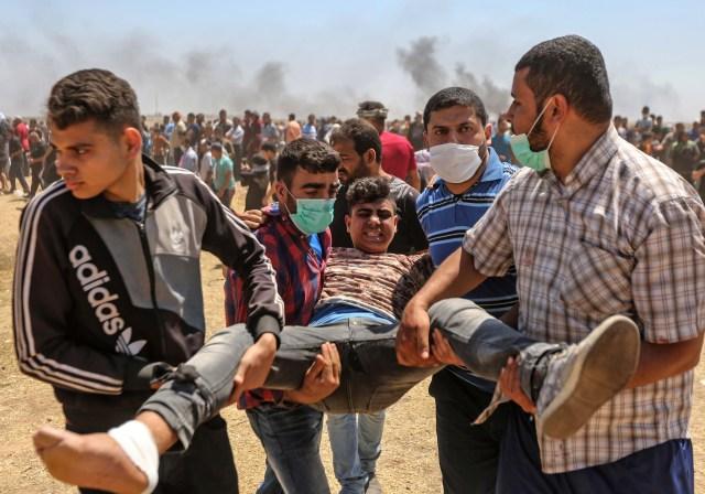Los palestinos llevan a un manifestante herido durante los enfrentamientos con las fuerzas israelíes cerca de la frontera entre la franja de Gaza e Israel al este de la ciudad de Gaza el 14 de mayo de 2018, durante una manifestación el día de la mudanza de la embajada de EE. UU. A Jerusalén. Docenas de palestinos fueron asesinados por disparos israelíes el 14 de mayo cuando decenas de miles protestaron y estallaron enfrentamientos a lo largo de la frontera de Gaza contra la transferencia de su embajada a Jerusalén, luego de meses de protestas globales, ira palestina y elogios exuberantes de los israelíes por el presidente Donald Trump decisión dejando de lado décadas de precedentes. / AFP PHOTO / MAHMUD HAMS