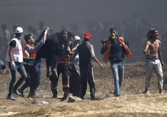 Los palestinos llevan a un manifestante herido durante enfrentamientos con fuerzas israelíes cerca de la frontera entre Gaza e Israel al este de la ciudad de Gaza el 14 de mayo de 2018, mientras los palestinos protestan por la inauguración de la embajada de Estados Unidos tras su controvertido traslado a Jerusalén. Docenas de palestinos fueron asesinados por disparos israelíes el 14 de mayo cuando decenas de miles protestaron y estallaron enfrentamientos a lo largo de la frontera de Gaza contra la transferencia de su embajada a Jerusalén, luego de meses de protestas globales, ira palestina y elogios exuberantes de los israelíes por el presidente Donald Trump decisión dejando de lado décadas de precedentes. / AFP PHOTO / Thomas COEX