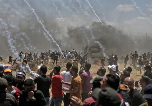 Los palestinos huyen del gas lacrimógeno durante los enfrentamientos con fuerzas israelíes cerca de la frontera entre Gaza e Israel al este de la ciudad de Gaza el 14 de mayo de 2018, mientras los palestinos protestan por la inauguración de la embajada de Estados Unidos tras su controvertido traslado a Jerusalén. Docenas de palestinos fueron asesinados por disparos israelíes el 14 de mayo cuando decenas de miles protestaron y estallaron enfrentamientos a lo largo de la frontera de Gaza contra la transferencia de su embajada a Jerusalén, luego de meses de protestas globales, ira palestina y elogios exuberantes de los israelíes por el presidente Donald Trump decisión dejando de lado décadas de precedentes. / AFP PHOTO / MAHMUD HAMS