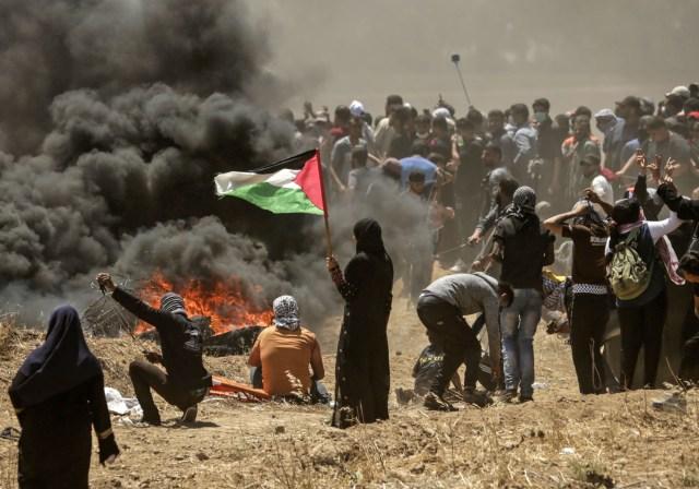 Una mujer palestina sosteniendo su bandera nacional observa los enfrentamientos con fuerzas israelíes cerca de la frontera entre Gaza e Israel al este de la ciudad de Gaza el 14 de mayo de 2018, mientras los palestinos protestan por la inauguración de la embajada de Estados Unidos tras su controvertido traslado a Jerusalén. Docenas de palestinos fueron asesinados por disparos israelíes el 14 de mayo cuando decenas de miles protestaron y estallaron enfrentamientos a lo largo de la frontera de Gaza contra la transferencia de su embajada a Jerusalén, luego de meses de protestas globales, ira palestina y elogios exuberantes de los israelíes por el presidente Donald Trump decisión dejando de lado décadas de precedentes. / AFP PHOTO / MAHMUD HAMS