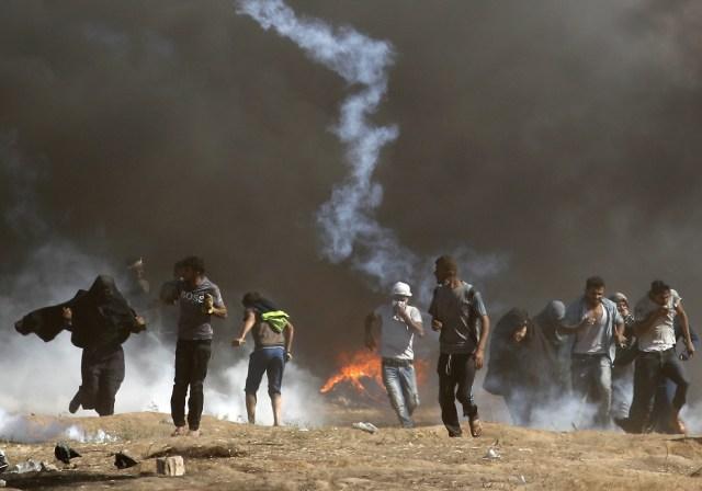 Los palestinos chocan con las fuerzas israelíes cerca de la frontera entre la franja de Gaza e Israel al este de la ciudad de Gaza el 14 de mayo de 2018, mientras los palestinos protestan por la inauguración de la embajada de Estados Unidos tras su controvertido traslado a Jerusalén. Docenas de palestinos fueron asesinados por disparos israelíes el 14 de mayo cuando decenas de miles protestaron y estallaron enfrentamientos a lo largo de la frontera de Gaza contra la transferencia de su embajada a Jerusalén, luego de meses de protestas globales, ira palestina y elogios exuberantes de los israelíes por el presidente Donald Trump decisión dejando de lado décadas de precedentes. / AFP PHOTO / Thomas COEX