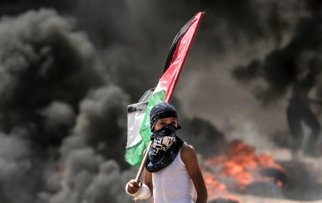 Un niño palestino sosteniendo su bandera nacional observa los enfrentamientos con las fuerzas de seguridad israelíes cerca de la frontera entre Gaza e Israel al este de la ciudad de Gaza el 14 de mayo de 2018, mientras los palestinos protestan por la inauguración de la embajada de Estados Unidos tras su controvertido traslado a Jerusalén. Docenas de palestinos fueron asesinados por disparos israelíes el 14 de mayo cuando decenas de miles protestaron y estallaron enfrentamientos a lo largo de la frontera de Gaza contra la transferencia de su embajada a Jerusalén, luego de meses de protestas globales, ira palestina y elogios exuberantes de los israelíes por el presidente Donald Trump decisión dejando de lado décadas de precedentes. / AFP PHOTO / MAHMUD HAMS