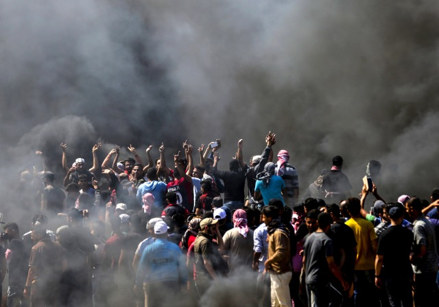 Los palestinos gritan consignas durante los enfrentamientos con las fuerzas de seguridad israelíes cerca de la frontera entre Gaza e Israel al este de la ciudad de Gaza el 14 de mayo de 2018, mientras los palestinos protestan por la inauguración de la embajada de Estados Unidos tras su controvertido traslado a Jerusalén. Docenas de palestinos fueron asesinados por disparos israelíes el 14 de mayo cuando decenas de miles protestaron y estallaron enfrentamientos a lo largo de la frontera de Gaza contra la transferencia de su embajada a Jerusalén, luego de meses de protestas globales, ira palestina y elogios exuberantes de los israelíes por el presidente Donald Trump decisión dejando de lado décadas de precedentes. / AFP PHOTO / MAHMUD HAMS