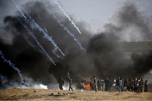 Se lanzaron gases lacrimógenos contra los manifestantes durante los enfrentamientos con las fuerzas israelíes cerca de la frontera entre la Franja de Gaza e Israel, al este de la ciudad de Gaza el 14 de mayo de 2018, tras el controvertido traslado a Jerusalén de la embajada de los Estados Unidos. Cincuenta y dos palestinos fueron asesinados por disparos israelíes durante violentos enfrentamientos en la frontera entre Gaza e Israel coincidiendo con la apertura de la embajada de Estados Unidos en Jerusalén, anunció el ministerio de salud en la franja.Fifty-two Palestinians were killed by Israeli fire during violent clashes on the Gaza-Israel border coinciding with the opening of the US embassy in Jerusalem, the health ministry in the strip announced.  / AFP PHOTO / THOMAS COEX