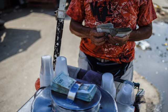 A peddler counts money in a street in Maracaibo, Venezuela on May 3, 2018. Amid blackouts, skyrocketing prices, shortage of food, medicine and transportation, Venezuelans go to elections next May 20 anguished to survive one of the worst crisis in the oil country. / AFP PHOTO / Federico PARRA