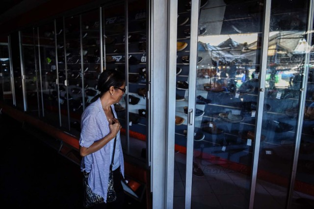 A woman looks at shoes in a store during a power outage in Maracaibo, Venezuela on May 3, 2018. Amid blackouts, skyrocketing prices, shortage of food, medicine and transportation, Venezuelans go to elections next May 20 anguished to survive one of the worst crisis in the oil country. / AFP PHOTO / Federico PARRA