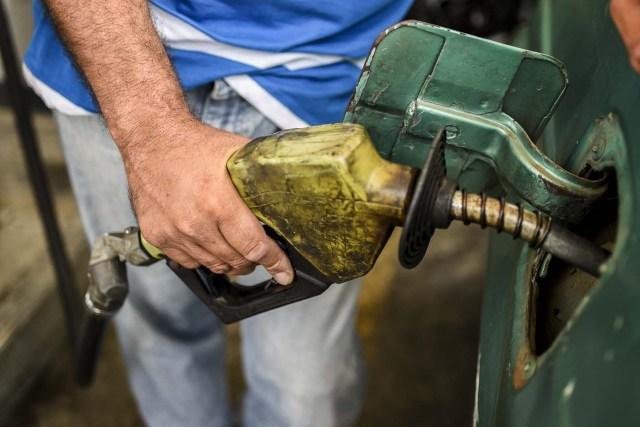 Un hombre surte de gasolina en Maracaibo, Venezuela / AFP PHOTO / Federico PARRA