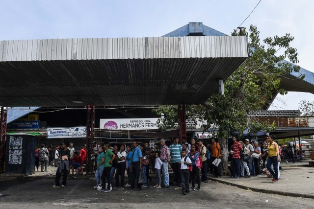 People wait for a transport in Maracaibo, Venezuela, on May 2, 2018. Amid blackouts, skyrocketing prices, shortage of food, medicine and transportation, Venezuelans go to elections next May 20 anguished to survive one of the worst crisis in the oil country. / AFP PHOTO / Federico PARRA