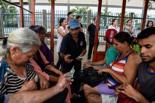 A man charges tickets to commuters using a children's train due to the lack of means of transportation on May 2, 2018, in Maracaibo, Venezuela. Amid blackouts, skyrocketing prices, shortage of food, medicine and transportation, Venezuelans go to elections next May 20 anguished to survive one of the worst crisis in the oil country. / AFP PHOTO / Federico PARRA