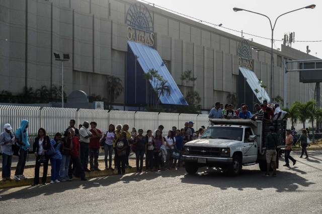 People wait to get on a truck used as a means of transportation in Maracaibo, Venezuela on May 3, 2018. Amid blackouts, skyrocketing prices, shortage of food, medicine and transportation, Venezuelans go to elections next May 20 anguished to survive one of the worst crisis in the oil country. / AFP PHOTO / Federico PARRA