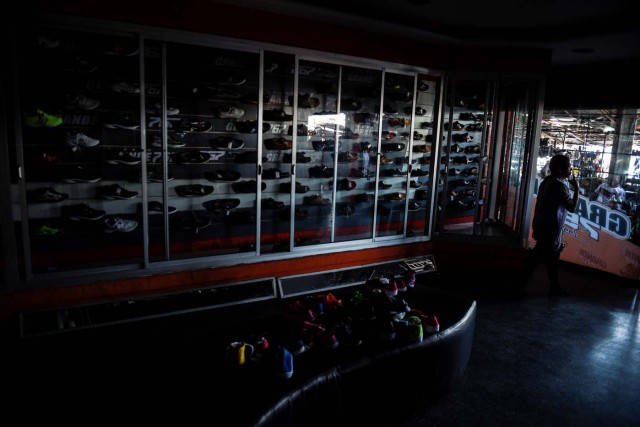 A man walks inside a store during a power outage in Maracaibo, Venezuela on May 3, 2018. Amid blackouts, skyrocketing prices, shortage of food, medicine and transportation, Venezuelans go to elections next May 20 anguished to survive one of the worst crisis in the oil country. / AFP PHOTO / Federico PARRA