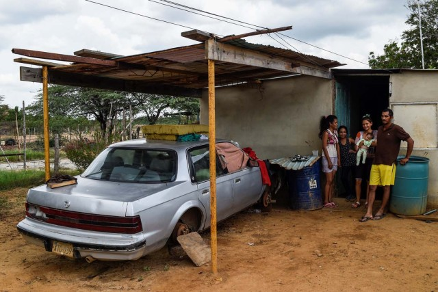A family stands next to their car out of use due to the lack of spare parts on May 2, 2018 in Maracaibo, Venezuela. Amid blackouts, skyrocketing prices, shortage of food, medicine and transportation, Venezuelans go to elections next May 20 anguished to survive one of the worst crisis in the oil country. / AFP PHOTO / Federico PARRA