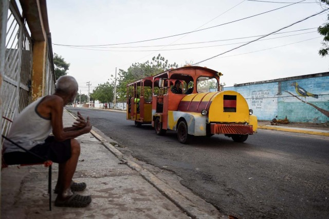 People travel in a children's train due to the lack of public transport on May 2, 2018, in Maracaibo, Venezuela. Amid blackouts, skyrocketing prices, shortage of food, medicine and transportation, Venezuelans go to elections next May 20 anguished to survive one of the worst crisis in the oil country. / AFP PHOTO / Federico PARRA