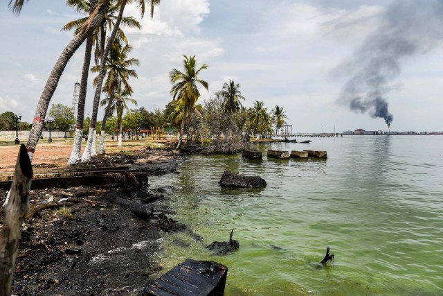 Remains of oil are seen at the shore of Maracaibo lake near to an oil refinery, on May 2, 2018 in Maracaibo, Venezuela. Amid blackouts, skyrocketing prices, shortage of food, medicine and transportation, Venezuelans go to elections next May 20 anguished to survive one of the worst crisis in the oil country. / AFP PHOTO / Federico PARRA
