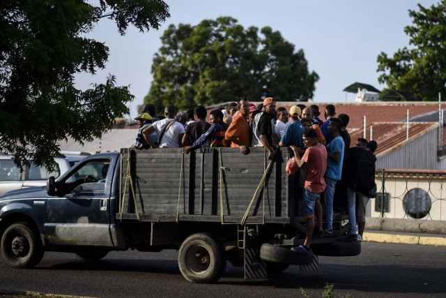 People travel on a private truck used as a means of transportation in Maracaibo, Venezuela on May 3, 2018. Amid blackouts, skyrocketing prices, shortage of food, medicine and transportation, Venezuelans go to elections next May 20 anguished to survive one of the worst crisis in the oil country. / AFP PHOTO / Federico PARRA