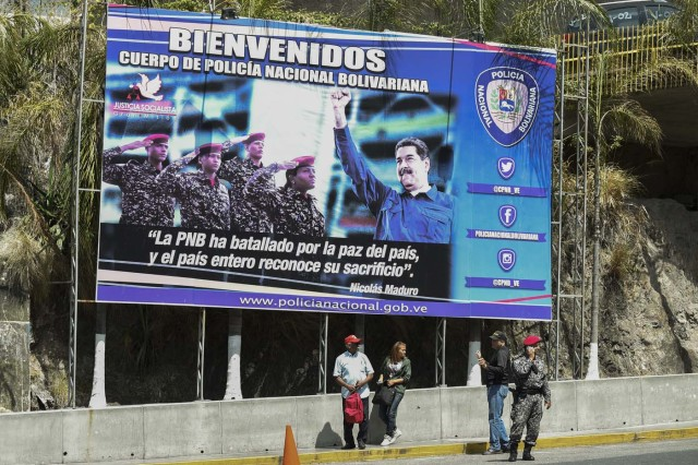 A poster with an image of Venezuela President Nicolas Maduro (R) is seen at the entrance of El Helicoide, the headquarters of the Bolivarian National Intelligence Service (SEBIN), in Caracas, on May 17, 2018, where Venezuelan opponents and a US citizen have seized control of the detention centre. The Venezuelan opponents and a US Mormon missionary, who took control of the cell block area on the eve, are demanding the release of prisoners, according to videos broadcast on social networks. / AFP PHOTO / Juan BARRETO