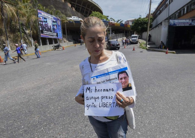 The sister of prisoner Jose Luis Santamaria demonstrates for his release at the entrance of El Helicoide, the headquarters of the Bolivarian National Intelligence Service (SEBIN), in Caracas, on May 17, 2018, where Venezuelan opponents and a US citizen have seized control of the detention centre. The Venezuelan opponents and a US Mormon missionary, who took control of the cell block area on the eve, are demanding the release of prisoners, according to videos broadcast on social networks. / AFP PHOTO / Juan BARRETO