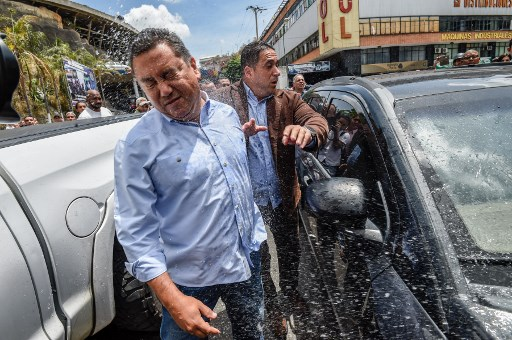 Venezuelan opposition presidential candidate and evangelical pastor Javier Bertucci (L) is thrown water by relatives of prisoners who didn't want candidates doing politics at El Helicoide, the headquarters of the Bolivarian National Intelligence Service (SEBIN), in Caracas, on May 17, 2018, where Venezuelan opponents and a US citizen have seized control of the detention centre. The Venezuelan opponents and a US Mormon missionary, who took control of the cell block area on the eve, are demanding the release of prisoners, according to videos broadcast on social networks. / AFP PHOTO / Juan BARRETO
