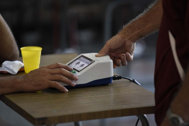 A man puts his finger on a fingerprint scanner after casting his ballot during the presidential elections in Caracas, Venezuela on May 20, 2018 Venezuelans, reeling under a devastating economic crisis, began voting Sunday in an election boycotted by the opposition and condemned by much of the international community but expected to hand deeply unpopular President Nicolas Maduro a new mandate / AFP PHOTO / Carlos Becerra