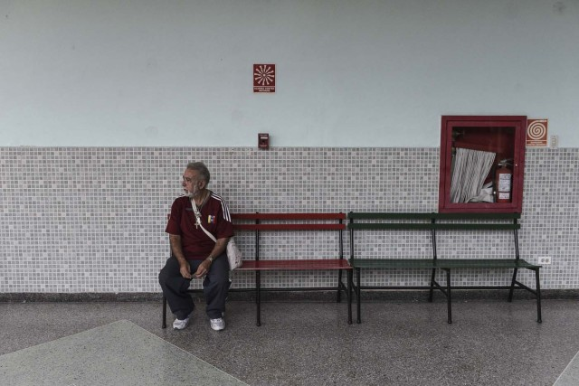 A Venezuelan man waits at an empty polling station during the presidential elections in Caracas on May 20, 2018 Venezuelans, reeling under a devastating economic crisis, began voting Sunday in an election boycotted by the opposition and condemned by much of the international community but expected to hand deeply unpopular President Nicolas Maduro a new mandate / AFP PHOTO / Carlos Becerra