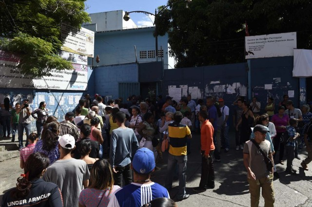 Venezuelans queue outside a polling station as they wait to cast their vote during the presidential elections in Caracas on May 20, 2018 Venezuelans headed to the polls early Sunday to vote in the general elections as incumbent president Nicolas Maduro is seeking a second term in power. / AFP PHOTO / Federico Parra