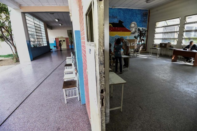A Venezuelan man votes in an empty polling station during the presidential elections in Caracas on May 20, 2018 Venezuelans, reeling under a devastating economic crisis, began voting Sunday in an election boycotted by the opposition and condemned by much of the international community but expected to hand deeply unpopular President Nicolas Maduro a new mandate / AFP PHOTO / Juan BARRETO