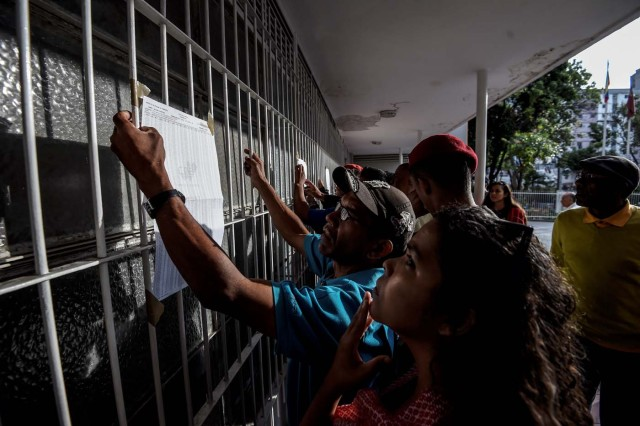 Venezuelans look for their names moments before casting their vote at a polling station during presidential elections in Caracas on May 20, 2018 Venezuelans, reeling under a devastating economic crisis, began voting Sunday in an election boycotted by the opposition and condemned by much of the international community but expected to hand deeply unpopular President Nicolas Maduro a new mandate / AFP PHOTO / Juan BARRETO
