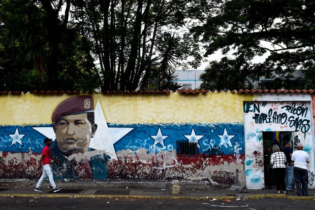 A man walks in front of an image of late Venezuelan president Hugo Chavez as peole wait to enter a polling station to cast their vote during the presidential elections in Caracas on May 20, 2018 Venezuelans, reeling under a devastating economic crisis, began voting Sunday in an election boycotted by the opposition and condemned by much of the international community but expected to hand deeply unpopular President Nicolas Maduro a new mandate / AFP PHOTO / FEDERICO PARRA