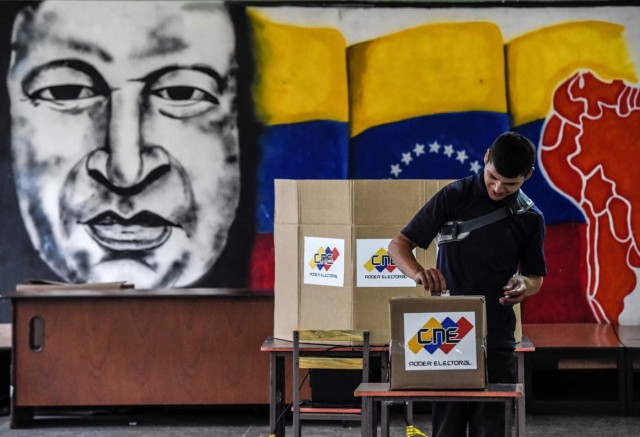 A man casts his vote in front of an image of late Venezuelan president Hugo Chavez, during the presidential elections at a polling station in Caracas on May 20, 2018 Venezuelans, reeling under a devastating economic crisis, began voting Sunday in an election boycotted by the opposition and condemned by much of the international community but expected to hand deeply unpopular President Nicolas Maduro a new mandate / AFP PHOTO / Juan BARRETO