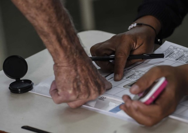 A man casts his vote during the presidential elections at a polling station in Caracas on May 20, 2018 Venezuelans, reeling under a devastating economic crisis, began voting Sunday in an election boycotted by the opposition and condemned by much of the international community but expected to hand deeply unpopular President Nicolas Maduro a new mandate / AFP PHOTO / Juan BARRETO