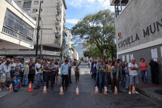 Venezuelans queue outside a polling station as they wait to cast their vote during the presidential elections in Caracas on May 20, 2018 Venezuelans, reeling under a devastating economic crisis, began voting Sunday in an election boycotted by the opposition and condemned by much of the international community but expected to hand deeply unpopular President Nicolas Maduro a new mandate / AFP PHOTO / Juan BARRETO