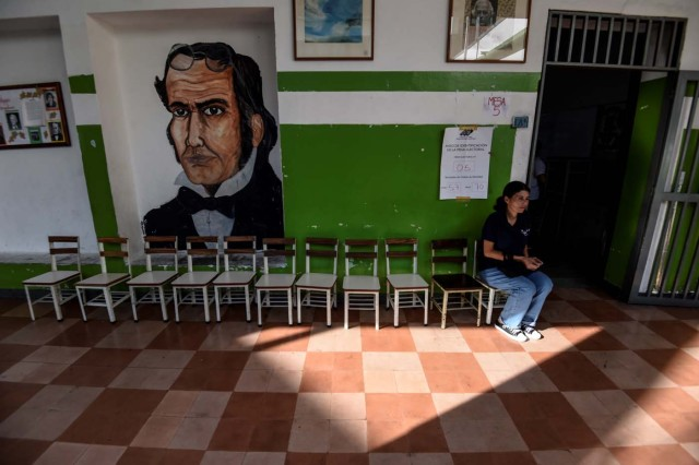 A Venezuelan woman waits at an empty polling station during the presidential elections in Caracas on May 20, 2018 Venezuelans, reeling under a devastating economic crisis, began voting Sunday in an election boycotted by the opposition and condemned by much of the international community but expected to hand deeply unpopular President Nicolas Maduro a new mandate / AFP PHOTO / Juan BARRETO
