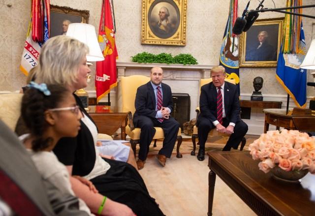El presidente estadounidense, Donald Trump, habla con la familia (L) de Joshua Holt (C), que estuvo detenido en Venezuela durante dos años, en la Oficina Oval en la Casa Blanca en Washington, DC, el 26 de mayo de 2018. / AFP PHOTO / NICHOLAS KAMM