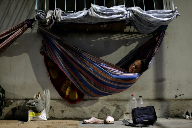 Venezuelan refugee Gabriela Martinez, who worked as a telecommunications engineer, relaxes in a hammock near a bus station in Manaus, Brazil May 1, 2018. Picture taken May 1, 2018. REUTERS/Bruno Kelly