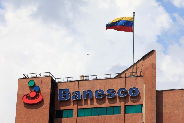 A Venezuelan flag waves above the corporate logo of Banesco bank at one of their office complexes in Caracas, Venezuela May 2, 2018. Picture taken May 2, 2018. REUTERS/Marco Bello