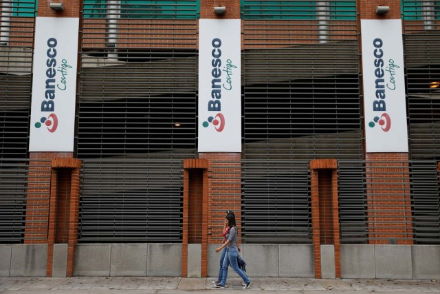 People walk past corporate logos of Banesco bank at one of their office complexes in Caracas, Venezuela May 3, 2018. REUTERS/Carlos Garcia Rawlins