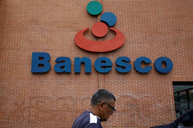 A man walks past the corporate logo of Banesco bank at one of its branches in Caracas, Venezuela May 3, 2018. REUTERS/Carlos Garcia Rawlins