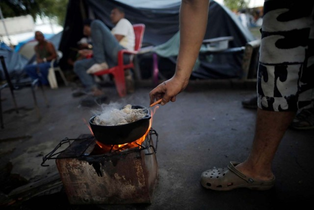 A Venezuelan migrant stands by a stove at a makeshift camp at Simon Bolivar square in Boa Vista, Brazil May 3, 2018. Picture taken May 3, 2018. REUTERS/Ueslei Marcelino