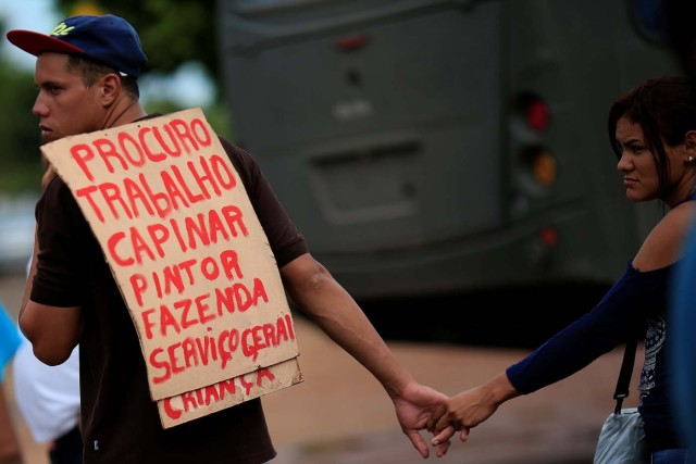 """A Venezuelan migrant uses a sign to apply for a job near a makeshift camp at Simon Bolivar square in Boa Vista, Brazil May 3, 2018. Picture taken May 3, 2018. The placard reads """"Looking for work, carpentry, painting, farming and general services."""" REUTERS/Ueslei Marcelino"""